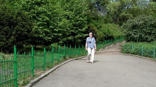 vídeos de stock, filmes e b-roll de um idoso com uma câmera caminha ao longo da avenida do parque primavera - calçada