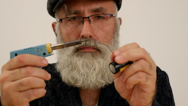 an elderly man with a white beard solder Close-up of male engineer working with a soldering iron in his hand. 4K beard stock videos & royalty-free footage