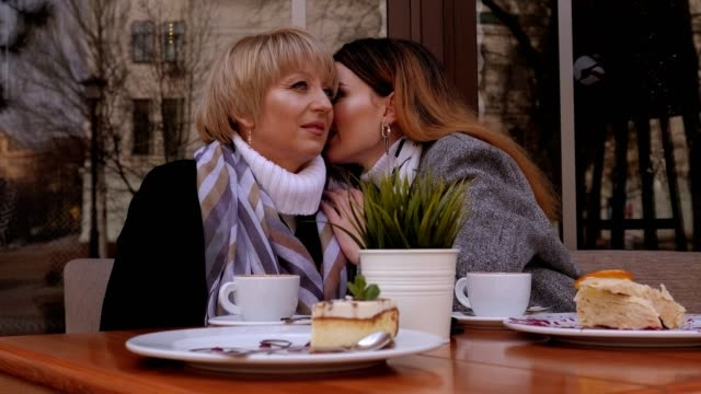an elderly mother and an adult daughter are talking in a street cafe. gossips. - ear talking video stock e b–roll