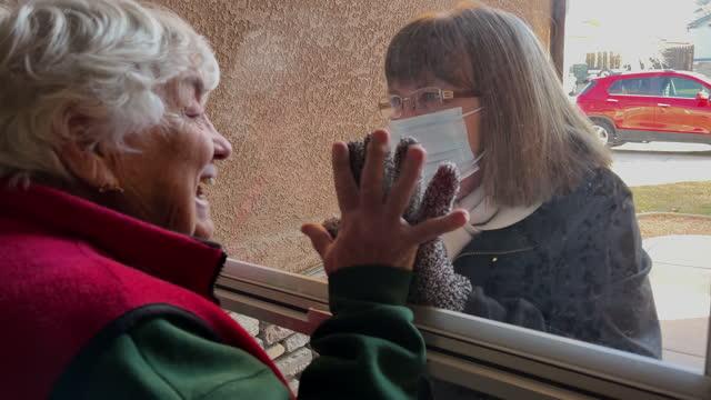 yaşlı bir anne uzun bir aradan sonra yetişkin kızını selamlıyor birbirlerini görmekten mutlu - ziyaret stok videoları ve detay görüntü çekimi