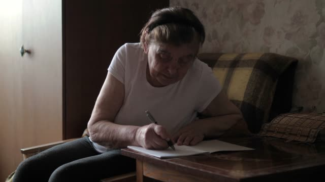 An Elderly Old Woman Writing Message On Paper Sitting At A Table