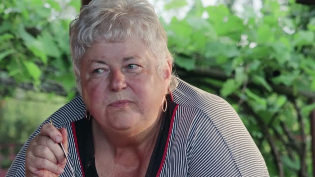 An elderly overweight woman eats an outdoor vegetable salad with a spoon and has a pensive look