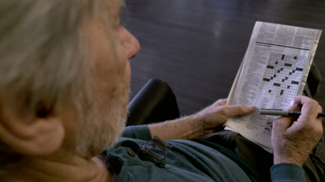 An elderly senior sits in a chair with a crossword puzzle in a newspaper OTS