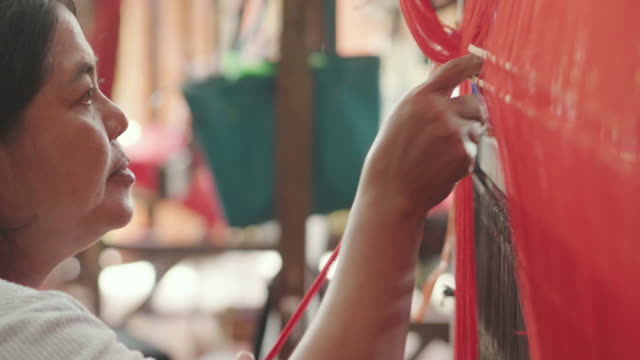 an elderly thai woman weaves clothes and produces hand-woven according to ancient tradition. - sarta video stock e b–roll