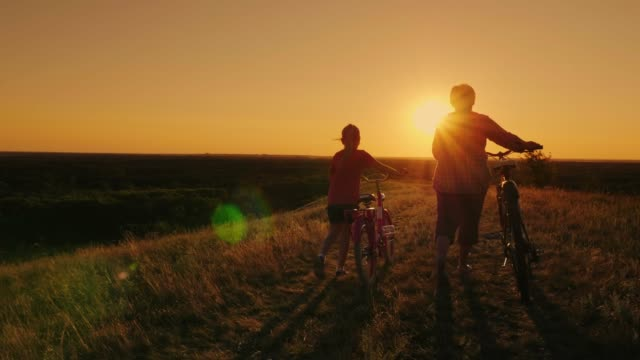 An elderly woman and girl 6 years together walk in a picturesque place, drive bicycles. Rear view at sunset An elderly woman is walking with her granddaughter in the countryside. They are walking alongside, driving bicycles. Concept - active elderly people granddaughter stock videos & royalty-free footage