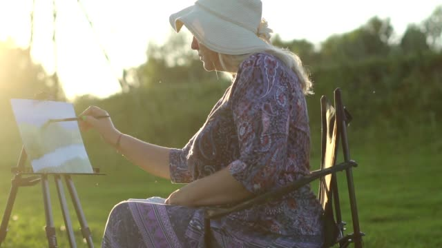 an elderly woman draws in nature video