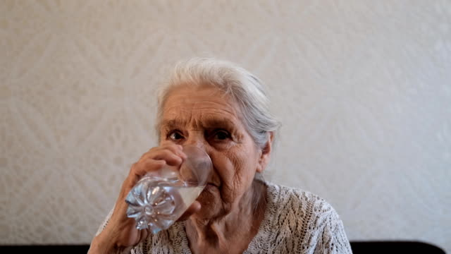 An elderly woman drinks water from a glass An elderly woman drinks water from a glass. 4K thirsty stock videos & royalty-free footage