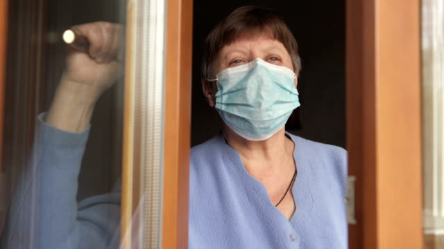 An elderly woman in a medical mask opens a window in a hospital. Quarantine self-isolation, coronavirus. video