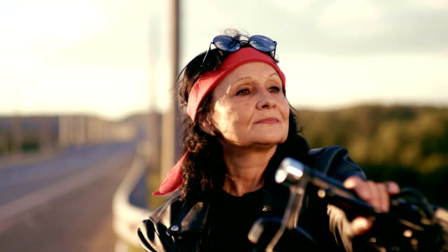 an elderly woman in a red scarf, leather jacket and gloves stands on the background of an empty road. puts his hands on his chest and shows the sign of bikers. the woman is smiling. happy life of an elderly rocker and biker after retirement - motociclista video stock e b–roll