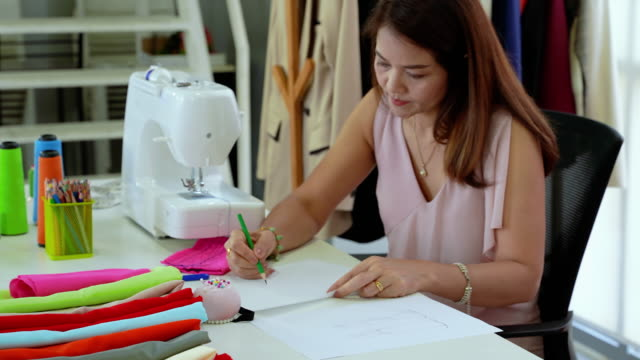 An elderly woman in an Asian occupation is a designer, drawing a picture for designing a garment.