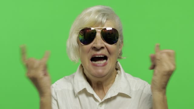 An elderly woman show sign of the horns with her hands and showing tongue An elderly woman show sign of the horns with her hands and showing tongue. Old pretty happy grandmother in sunglasses and white shirt. Place for your logo or text. Chroma key. Green screen background rock music stock videos & royalty-free footage