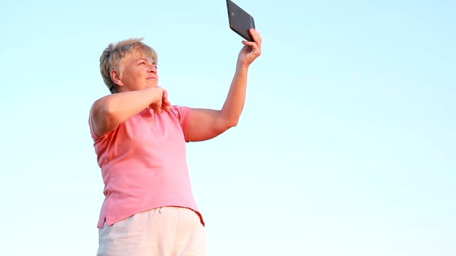 an elderly woman waves into the camera of the tablet video