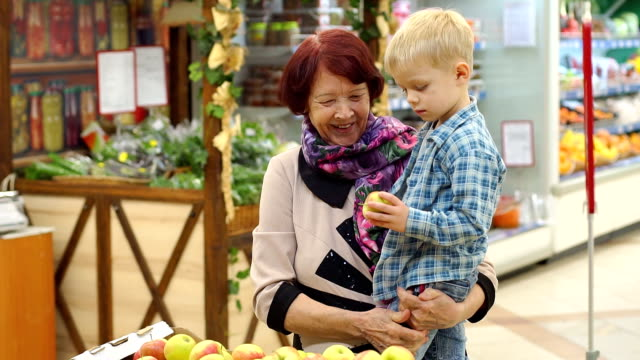 An elderly woman with her little grandson buy fresh apples in large supermarket. An elderly woman with her little grandson buy fresh apples in a large supermarket. Grandmother and child make purchases at the grocery store. granddaughter stock videos & royalty-free footage