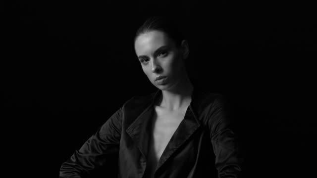 en elegant ung kvinna i svart jacka ser trotsigt på kameran. svartvit video. - blazer bildbanksvideor och videomaterial från bakom kulisserna