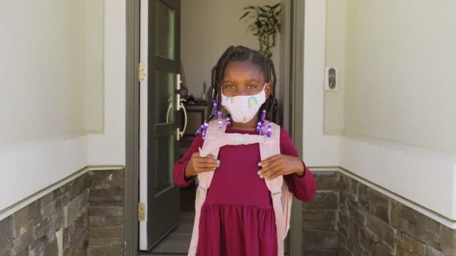 vidéos et rushes de un élève d'école primaire allant à l'école avec le masque de visage - enfant masque