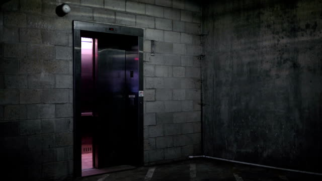 an elevator door closes in the basement ground level of dark parking garage - basement stock videos & royalty-free footage