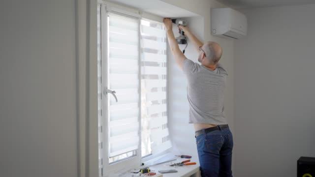 vídeos de stock e filmes b-roll de an employee for an hour makes minor repairs in a newly built apartment, he hangs on the window blinds - obras em casa janelas