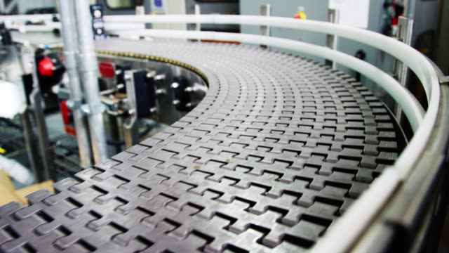 an empty conveyor belt moves down the production line in an indoor manufacturing facility - metal robot in logistic factory video stock e b–roll