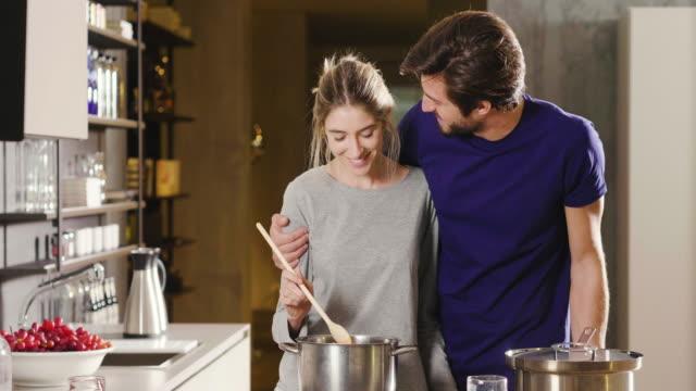 vidéos et rushes de un couple fiancé cuisine ensemble et s'amuse tout en dégustant la sauce qu'ils ont préparée. le couple se embrasse pour montrer leur amour. - cuisine non professionnelle