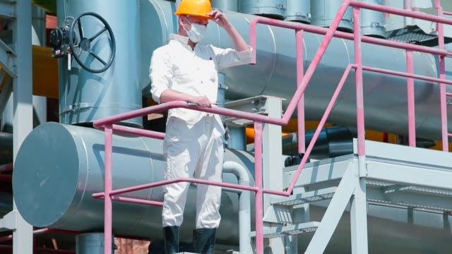 An engineer in white clothes in mask on his face went to gas production platform