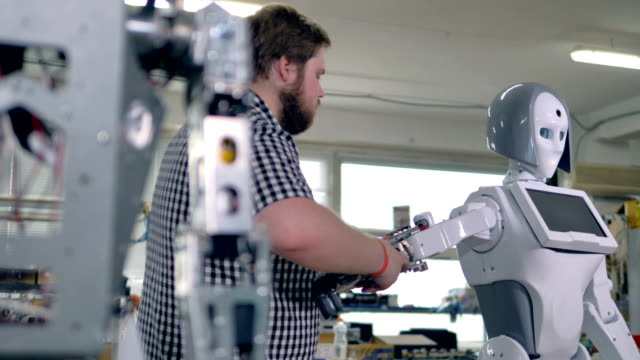 An engineer lifts a robots arm to add screw nuts in their slots. 4K. video