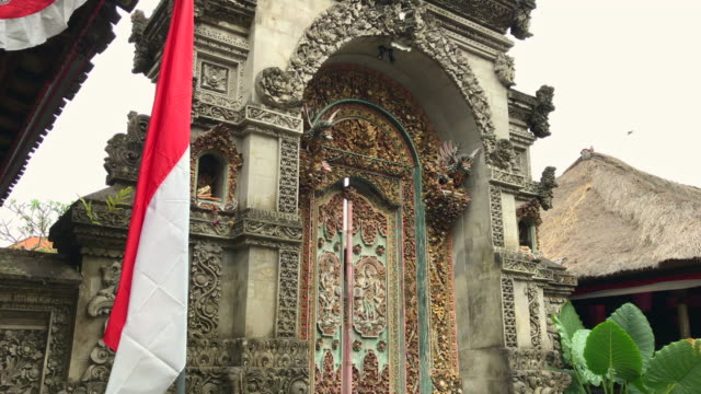 An entrance to a traditional Balinese house. Door with wood carving and stone carving. Shot on a phone