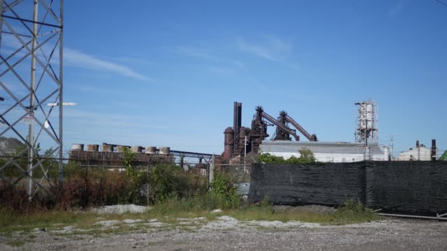An establishing shot of a old gritty blast furnace factory - vídeo