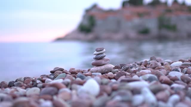 vídeos de stock e filmes b-roll de an even pile of pebbles on a pebble beach near the water - filosofia
