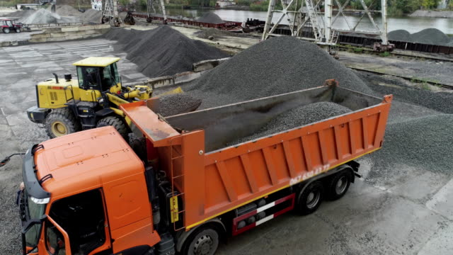 an excavator loads rubble in a truck body, loading a truck aerial view - ghiaia video stock e b–roll