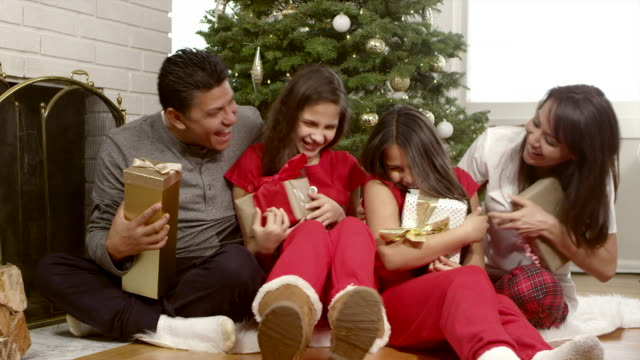 An excited family holds their christmas presents while sitting under the tree video