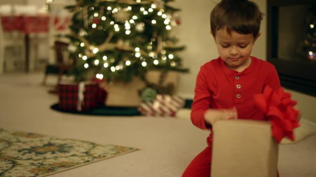 en upphetsad fem - årig kaukasiska pojke öppnar en julklapp av julgranen på juldagen - christmas gift family bildbanksvideor och videomaterial från bakom kulisserna
