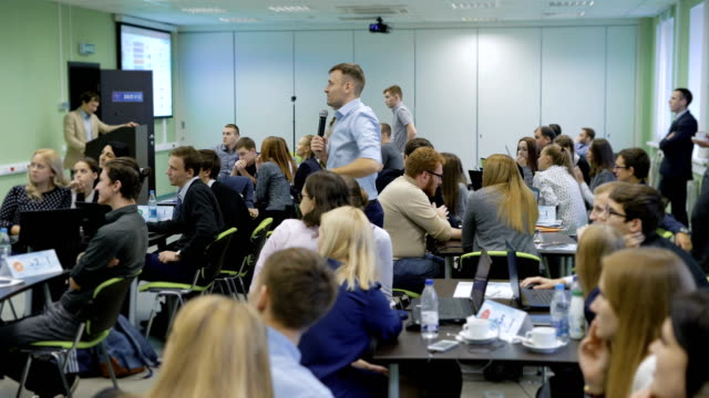 an experienced business coach, speaking at a conference in front of a large number of managers. man shows the image from the projector and comments them. large modern rooms for conferences - train stock videos and b-roll footage