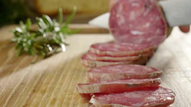 vídeos y material grabado en eventos de stock de un experimentado chef en una cocina profesional corta el experimentado. salchichas de salami italiano il se cortan con un cuchillo profesional con rebanadas muy delgadas. - carne