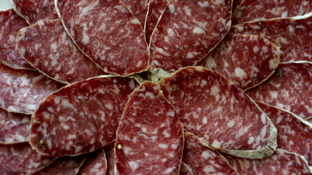 An experienced chef in a professional kitchen cuts the seasoned.Il Italian salami sausage is cut with a professional knife with very thin slices. video