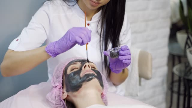 An experienced cosmetologist carefully applies a black cleansing mask to a woman's face in a beauty salon.