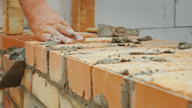 an experienced worker makes a brick wall masonry - mattone video stock e b–roll