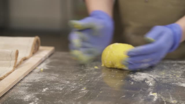an expert baker rounding and shaping dough into classic bread loafs and placing it onto a tray for fermentation rest before baking - formare pane video stock e b–roll