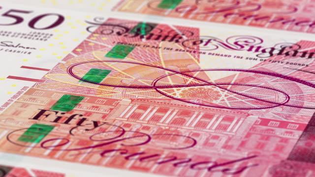 eine extreme nahaufnahme kamera schwenken über mehrere bank of england 50 pfund sterling banknoten - nahtlose schleife - pfand stock-videos und b-roll-filmmaterial