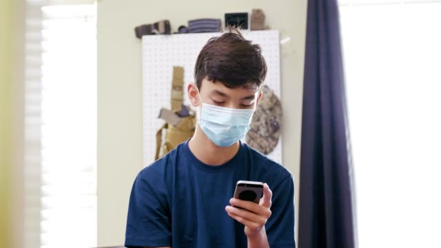 An ill teenage boy uses smartphone in his room An ill teenage boy wears a face mask to prevent family members from getting sick. He is using a smartphone while recovering in his room. independence stock videos & royalty-free footage