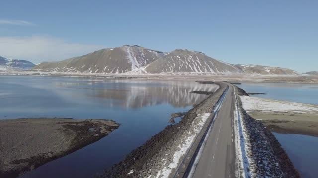 運河や湖の真ん中に橋を渡る車の信じられないほどの眺めは、甘い水から海を分離します。山を背景に晴れた日にアイスランドの環状道路に沿って - 空中、アイスランド - 陸の乗り物点の映像素材/bロール