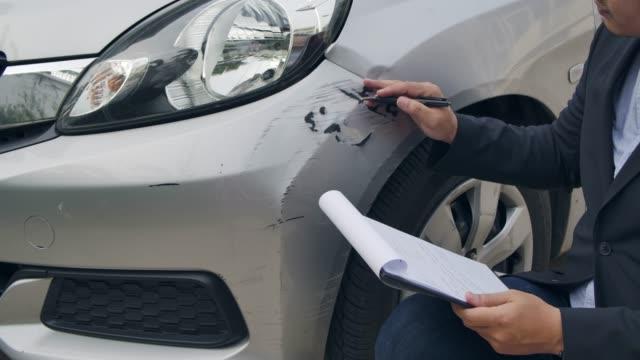 en försäkrings agent inspekterar en bil. - försäkring bildbanksvideor och videomaterial från bakom kulisserna