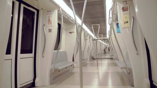 an interior view of modern white long subway train driving in high speed underground everyday. half-empty metro approaching to the station in the city of rome. people getting up and are ready to get out from the subway train - wagon kolejowy filmów i materiałów b-roll