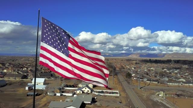 vidéos et rushes de un grand drapeau américain volant sur une journée d'automne magnifique - patriotisme