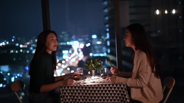 an LGBT couple enjoying their drink with city view at background at night on candlelight date