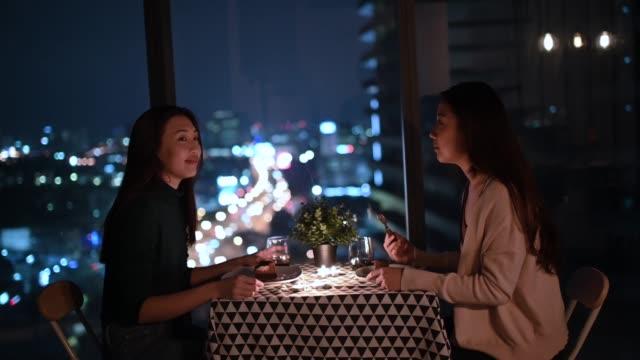 stockvideo's en b-roll-footage met een lgbt paar dat van hun drank met stadsmening bij achtergrond bij nacht op date bij kaarslicht geniet - dineren