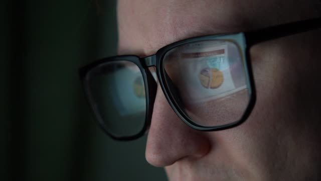 an office worker sits at the computer, a monitor with tables and graphs is reflected in the glasses - scienziato video stock e b–roll
