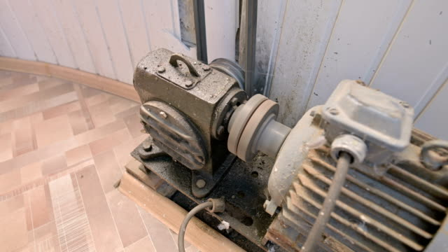 An old electric motor covered with dust and dirt turns a two-thread pulley through a cardan gearbox with a belt drive to another mechanism. The concept of old electro engines and equipment
