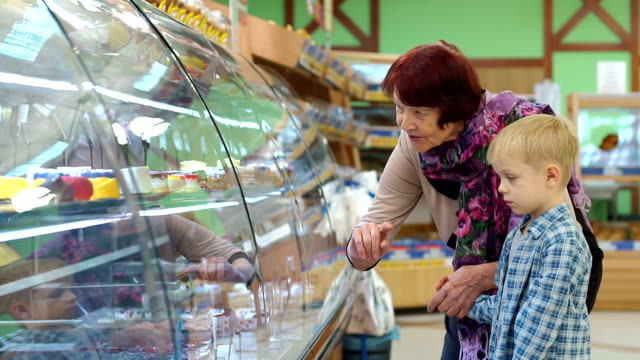 an old grandmother with a small grandson in the supermarket choose sweets. - deser filmów i materiałów b-roll