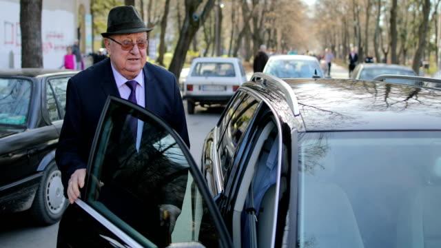 彼の頭に帽子をかぶった老人が車に入る ビデオ