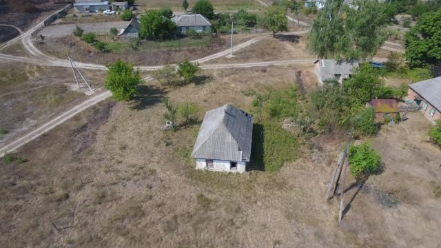 An old one-story house in a Ukrainian village aerial view. The drone flies around a detached house in the village. Near the pine forest. prop stock videos & royalty-free footage